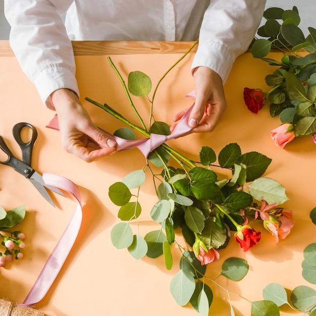 Close-up fleuriste faisant un ruban pour bouquet Photo gratuit