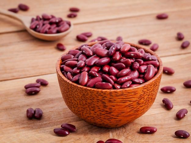 Close up haricots rouges dans un bol en bois Photo Premium