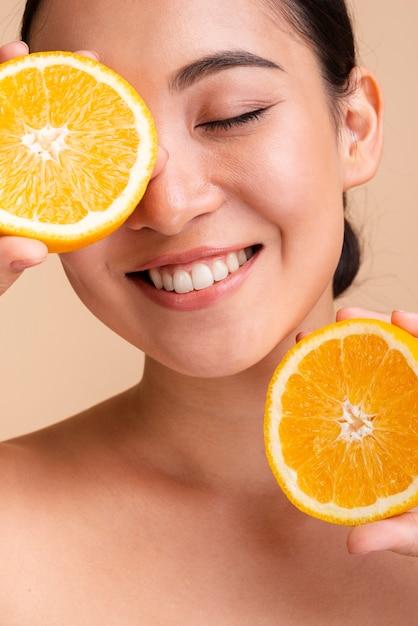 Close-up heureuse femme asiatique avec orange Photo gratuit