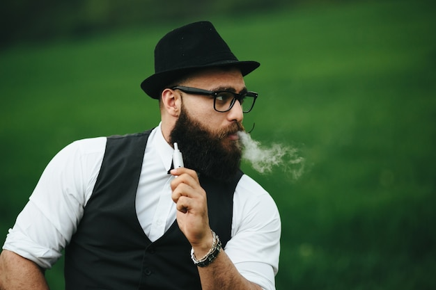 Close-up de l'homme avec un chapeau de fumer un cigare électronique Photo gratuit