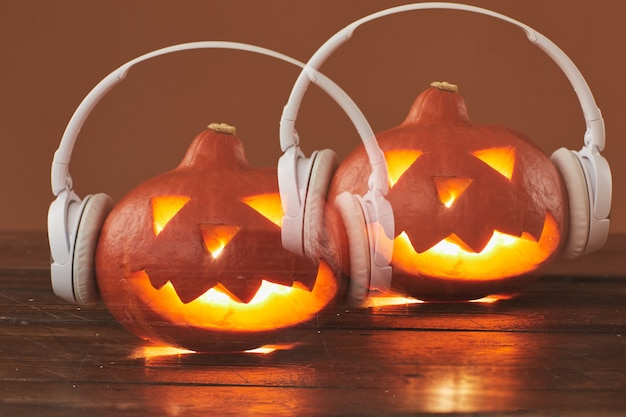 Close-up Horizontal Exposition Multiple Studio Shot De Jack O 'lantern Portant Des écouteurs Blancs Contre La Surface Brune Photo Premium