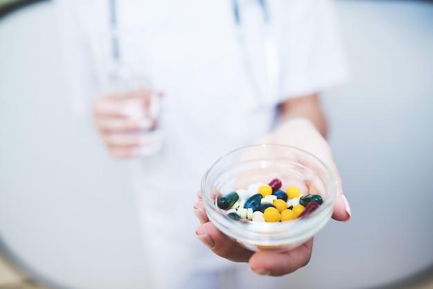 Close up une infirmière tient diverses pilules dans ses mains Photo Premium