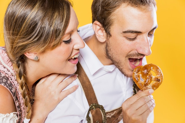 Close-up jeune couple mangeant un bretzel Photo gratuit