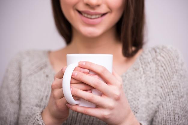 Close-up jeune femme tient une tasse de thé. Photo Premium