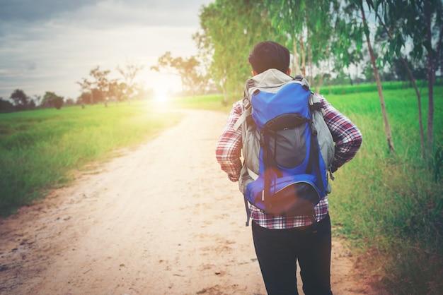 Close up jeune homme hipster avec sac à dos sur son pied d'épaule Photo gratuit