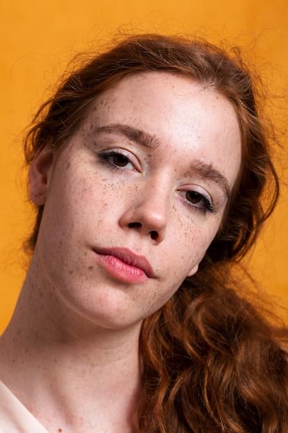 Close-up jolie femme avec des taches de rousseur et des yeux bruns Photo gratuit