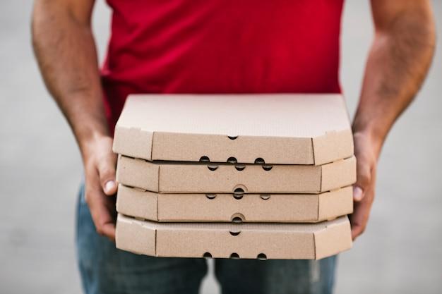 Close-up livreur tenant la commande de pizza Photo gratuit
