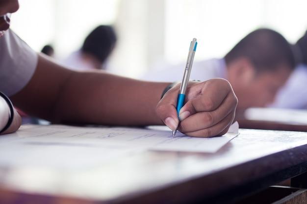 Close-up main d'étudiants écrivant un examen en salle de classe avec le stress Photo Premium