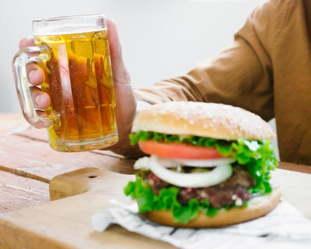 Close-up man boire de la bière et manger un hamburger Photo gratuit