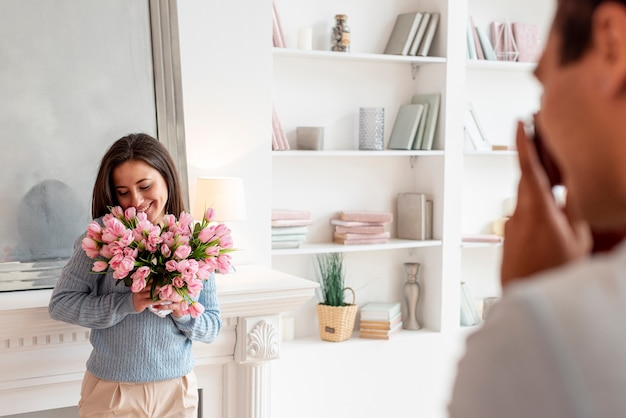 Close-up man surprenant femme avec des fleurs Photo gratuit
