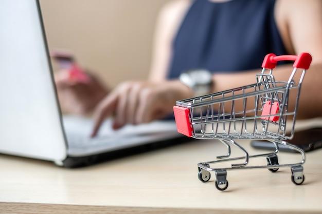 Close up mini cart, femme d'affaires asiatique détenant la carte de crédit et à l'aide d'un ordinateur portable Photo Premium