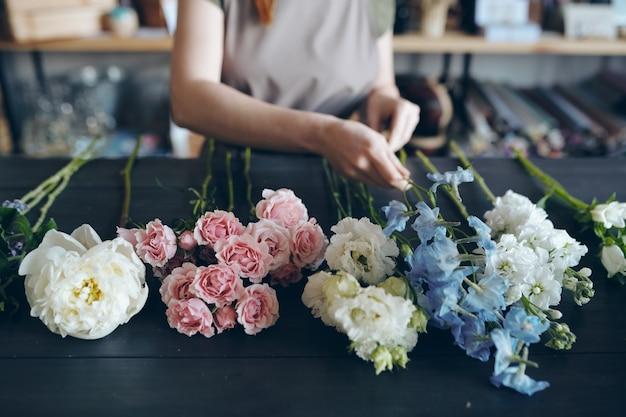 Close-up Of Fleuriste Méconnaissable Debout à Table En Bois Bleu Foncé Et Préparation De Fleurs Pour Organiser Le Bouquet Photo Premium