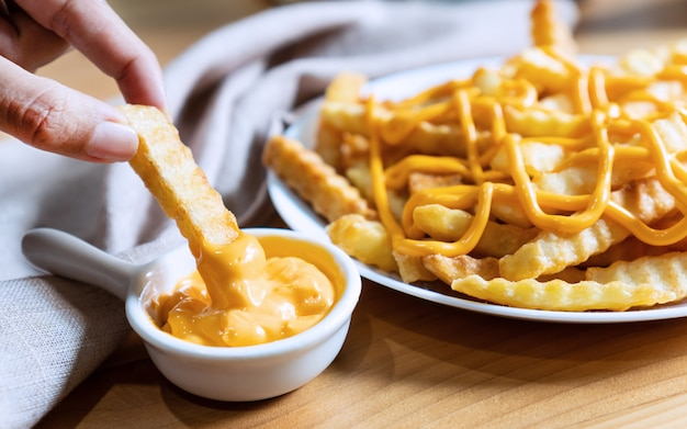 Close Up Of Hand Holding French Fries Dip Cheese With French Fries In White Dish Derrière Sur Une Table En Bois. Photo Premium