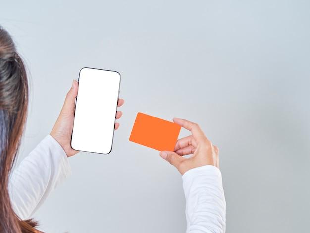 Close-up Of Woman Hold Smartphone, écran Vide Et Carte Bancaire De Crédit Sur Fond Gris Photo Premium