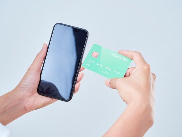 Close-up Of Woman Hold Téléphone Mobile, écran Vide Et Carte Bancaire De Crédit Sur Fond Gris Photo Premium