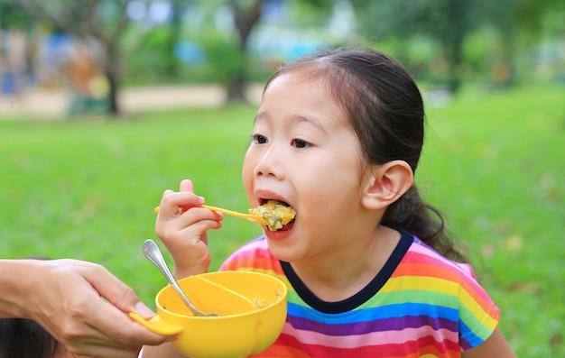Close-up petite fille asiatique enfant âgé d'environ 4 ans mangeant du riz par soi-même dans le jardin en plein air. Photo Premium