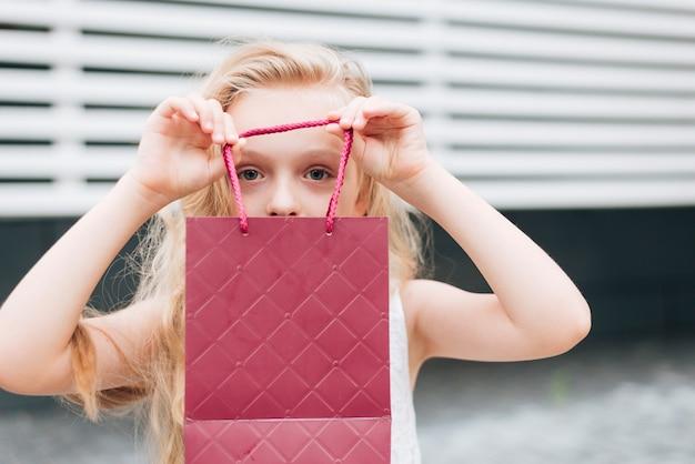 Close-up Petite Fille Tenant Un Sac Cadeau Photo gratuit