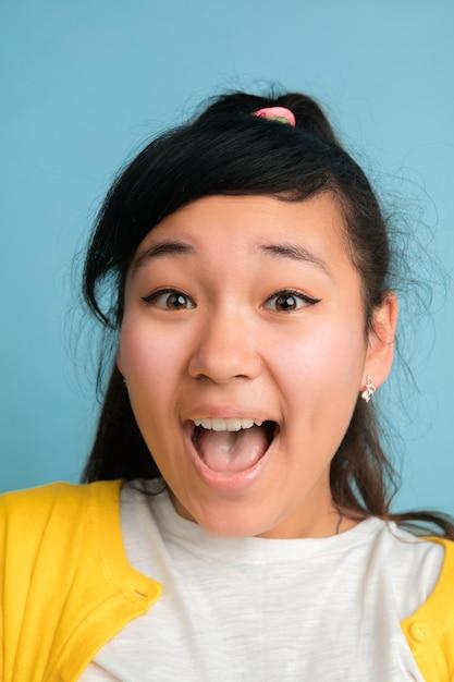 Close Up Portrait De L'adolescent Asiatique Isolé Sur Fond Bleu Studio Photo gratuit