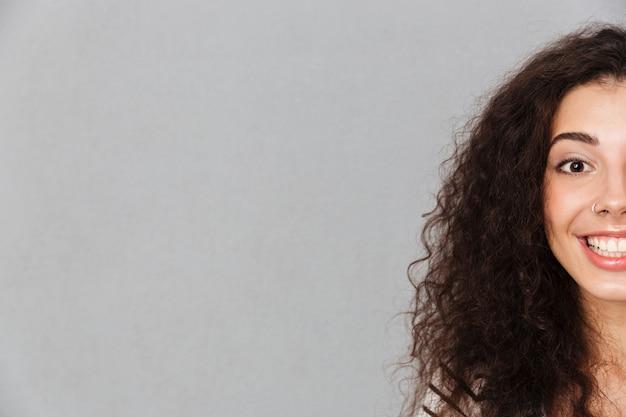 Close Up Portrait De Demi Visage De Jolie Femme Bouclée Avec Anneau Dans Le Nez Posant Souriant Avec Des Dents Blanches Parfaites Sur Mur Gris Photo gratuit