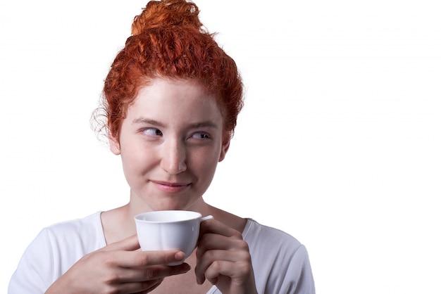 Close-up portrait de fille aux cheveux rouges avec des taches de rousseur buvant dans une tasse Photo Premium