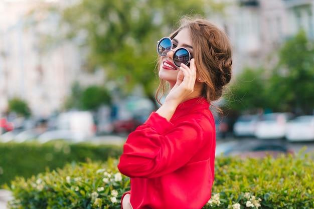 Close-up Portrait De Jolie Fille à Lunettes De Soleil Posant à La Caméra Dans Le Parc. Elle Porte Un Chemisier Rouge Et Une Belle Coiffure. Elle Regarde Au Loin. Photo gratuit