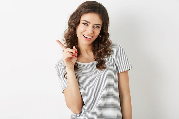 Close Up Portrait Of Attractive Young Woman Smiling Face Expression Holding Finger Up, Montrant De Côté`` Beauté Naturelle, T-shirt, Dents Blanches, Isolé Sur Fond Blanc, Gesticulant Photo gratuit