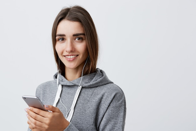 Close Up Portrait Of Beautiful Happy Dark-haired Caucasian Woman In Casual Gray Hoodie Smiling, Holding Cellphone In Hands, Listen Music In Earphones Photo gratuit
