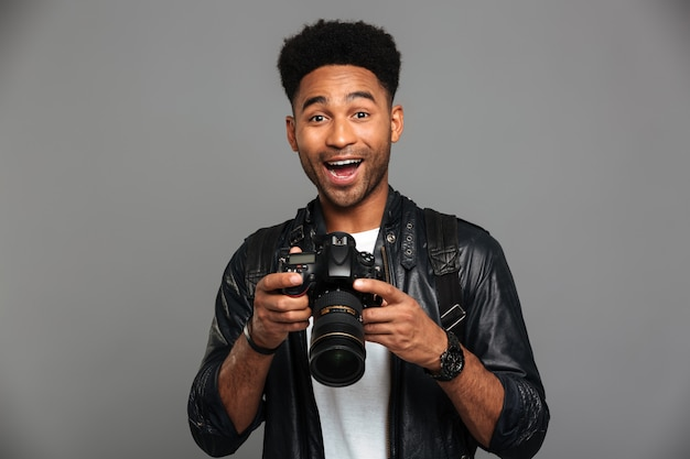 Close-up Portrait Of Happy Afro American Man Holding Photocamera Photo gratuit
