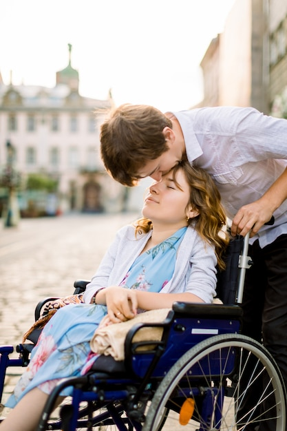 Close-up Portrait Of Happy Young Woman In Wheelchair And Her Mari Kissing Her Front, Walking Outdoors In Old City Photo Premium