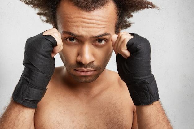Close Up Portrait Of Male Boxer Montre Des Bras Forts Et Les Poings Serrés Enveloppés Par Des Bandages Protecteurs Photo gratuit