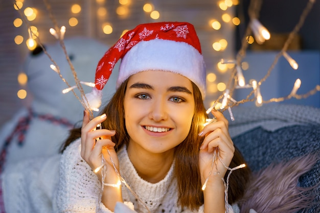 Close-up Portrait Of A Smiling Cute Young Woman With A Santa Hat On Her Head With Garlands In Her Hands Photo Premium
