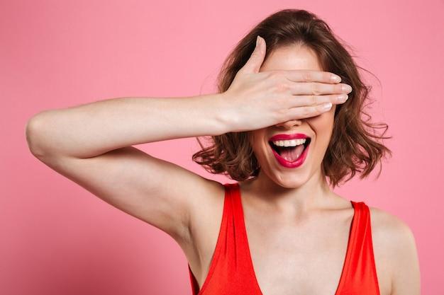 Close-up Portrait Of Smiling Smiling Brunette Woman Cachant Les Yeux Sous La Main Photo gratuit