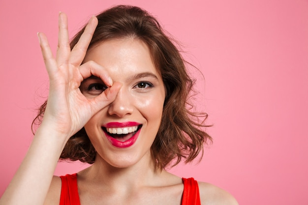 Close-up Portrait Of Young Happy Girl With Red Lips Through Ok Sign Photo gratuit