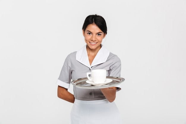 Close-up Portrait Of Young Smiling Female Waiter In Uniform Holding Metal Tray With Cup Of Coffee Photo gratuit