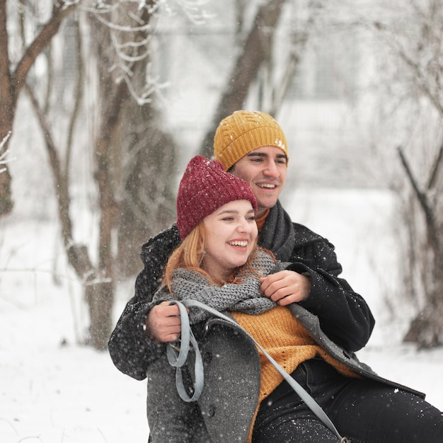 Close-up Smiley Couple Assis Dans La Neige En Plein Air Photo gratuit