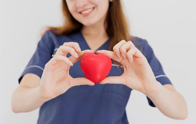 Close-up smiley docteur tenant jouet en forme de coeur Photo gratuit