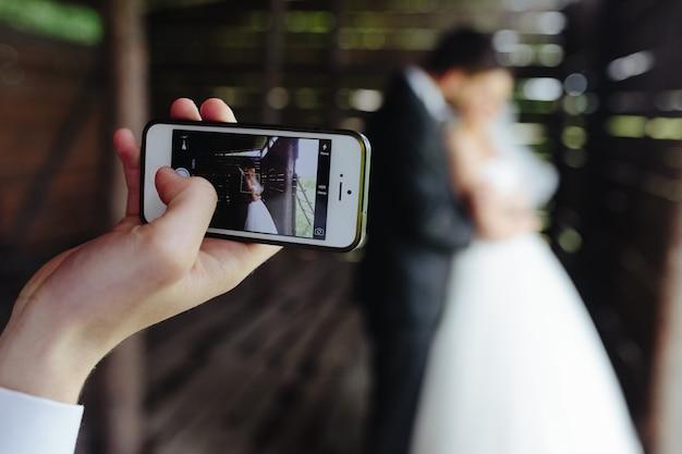 Close-up de la téléphonie mobile de prendre une photo des jeunes mariés Photo gratuit