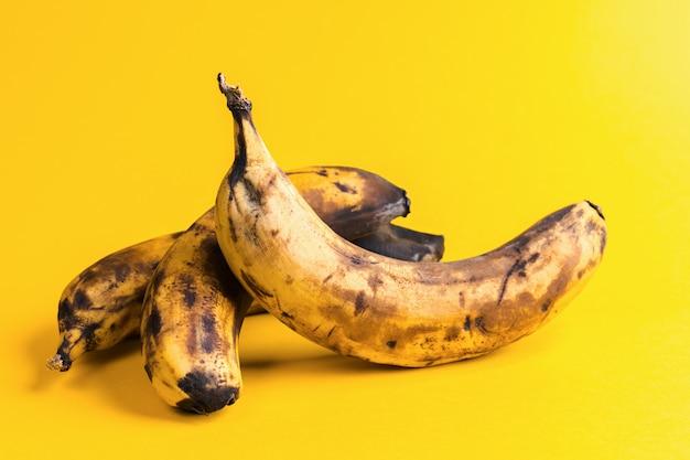 Close-up trois bananes laides noircies surmûres sur fond jaune. Photo Premium