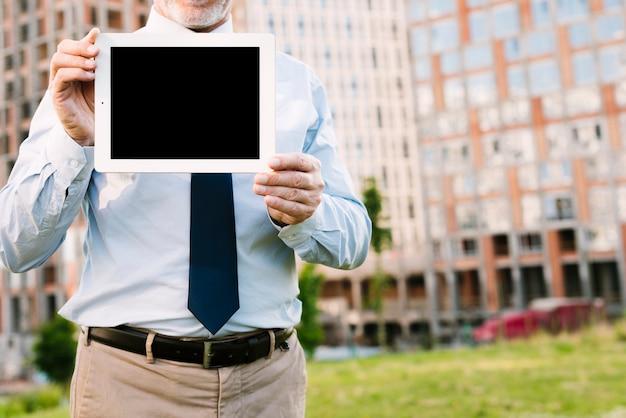 Close-up vieil homme avec tablette maquette Photo gratuit