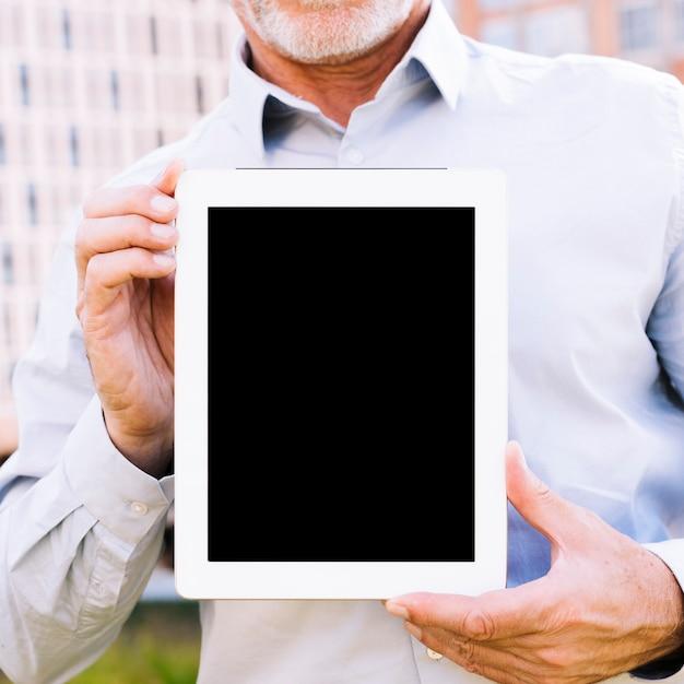 Close-up vieil homme tenant une maquette de tablette Photo gratuit