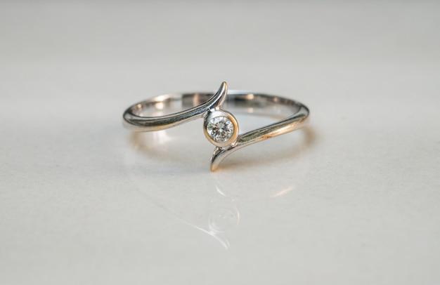 Closeup ancien diamant bague sur fond de sol en marbre floue Photo Premium