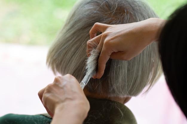 Closeup Barbier Avec Des Ciseaux Coupe Les Cheveux Photo Premium