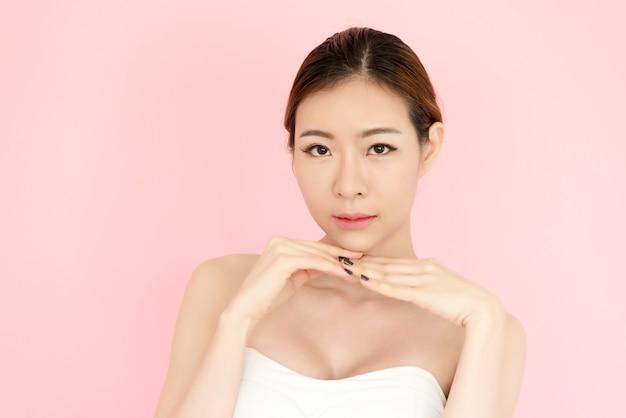 Closeup belle jeune femme asiatique visage isolé sur rose Photo Premium