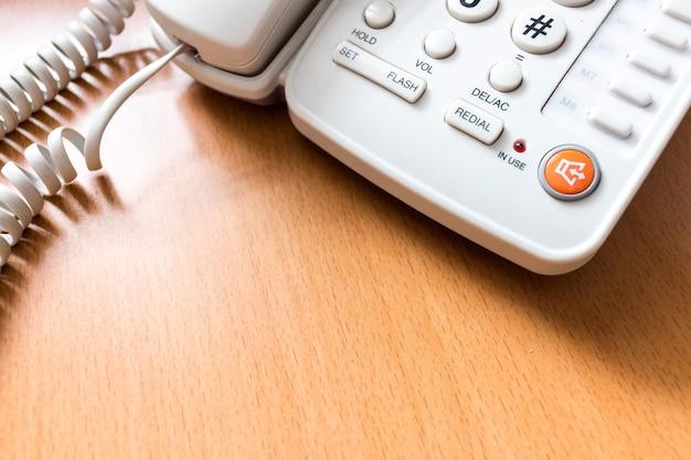 Closeup blanc téléphone sur le bureau avec flou artistique et plus de lumière en arrière-plan Photo Premium
