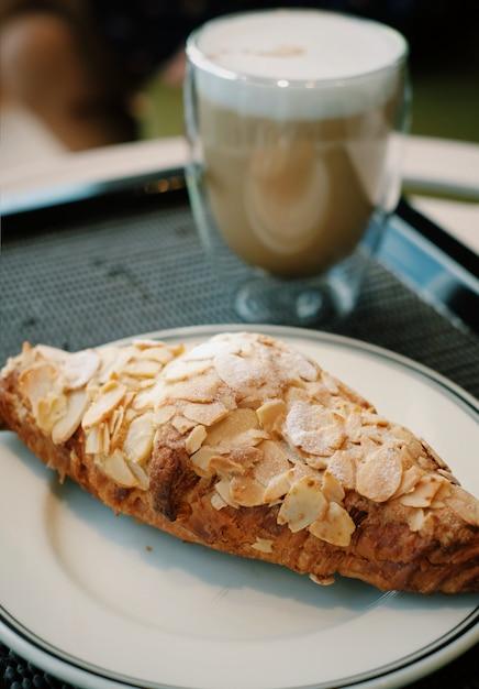 Closeup croissant aux amandes avec fond de café chaud Photo Premium