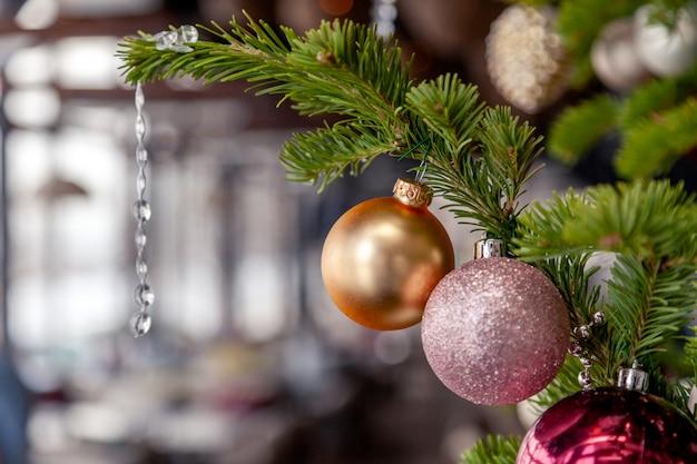 Closeup décoration de noël, nouvel an, branches épinette de sapin avec boules dorées et roses de jouets de fête brillants. Photo Premium