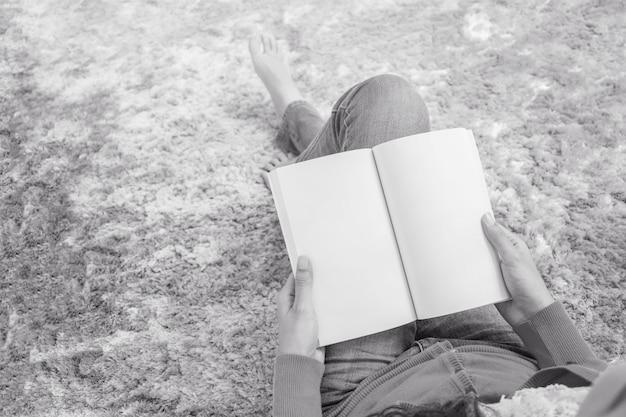 Closeup, femme asiatique, séance, sur, gris, tapis, à, plancher, dans, les, maison, fond texturé, pour, lire livre, dans, temps relâche Photo Premium