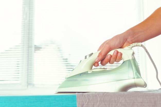 Closeup, femme, repasser, vêtements, planche repasser Photo Premium