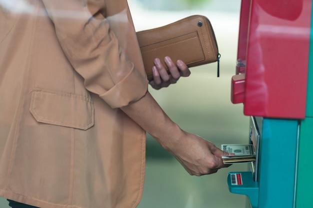 Closeup femme tenant le portefeuille et retirer de l'argent via un guichet automatique Photo Premium