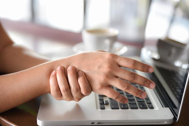 Closeup femme tenant sa douleur à la main d'utiliser un ordinateur longtemps. notion de syndrome de bureau. Photo Premium
